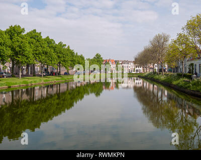 calm canal through Middelburg with trees and hedges on the sides on the island Walcheren, Zeeland, Netherlands - Stock Photo