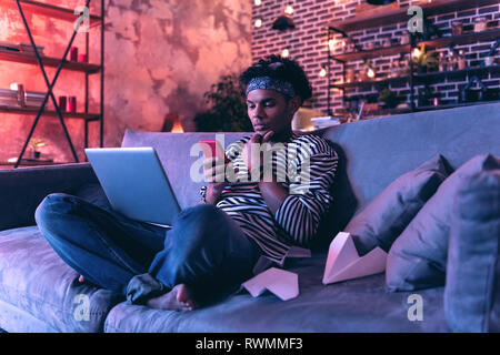 African American teenager with laptop and smartphone in the hand trying to watch video and study at the same time. - Stock Photo