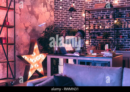 Young man standing near the table with a laptop and flying paper planes instead of working. - Stock Photo