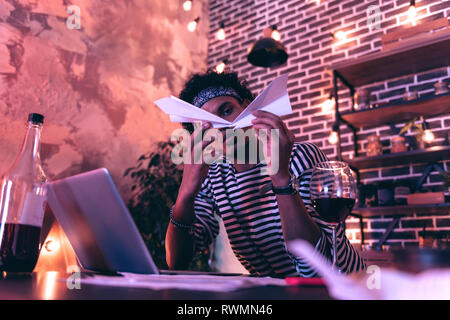 Young man imitating air crash, while glass and a bottle of wine standing right next to him. - Stock Photo