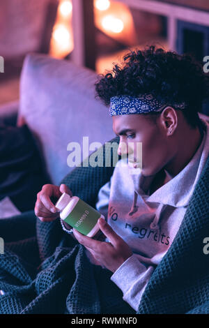 Young patient examining the composition of vitamins prescribed by a doctor reading a text on bottle. - Stock Photo
