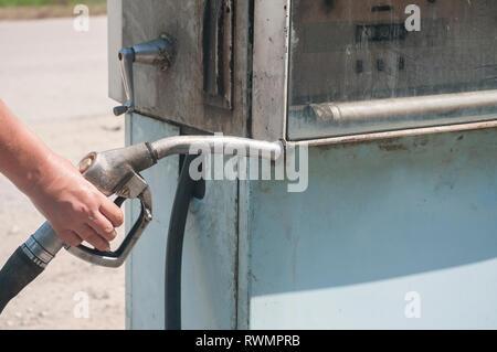 Old abandoned vintage obsolete petrol fuel gas dispenser in former petrol station and human hand holding petrol fuel dispenser handle - Stock Photo