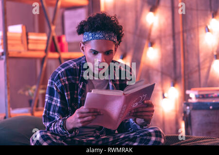 Confused boy revealing the secrets that the book hid from everyone. - Stock Photo