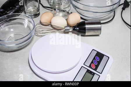 Digital kitchen scales and bowl closeup on a white table. - Stock Photo