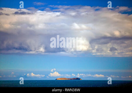 View of a cloudy sky over a calm sea with an island on the horizon. - Stock Photo