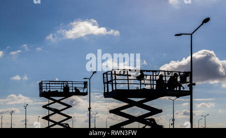 Street lamp repair workers on lift platform - Stock Photo