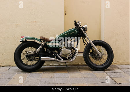 Green custom Honda motorcycle with the name Massey Ferguson in gold lettering on the fuel tank parked on a street in Toulon. - Stock Photo