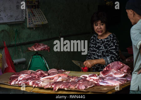 Butcher and customer chatting as raw meat is prepared in an open air low hygiene setting, Melaka, Malaysia. - Stock Photo