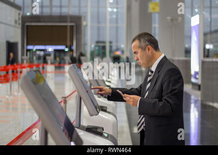 Passenger business man at the airport check in ticket at kiosk terminal - Stock Photo