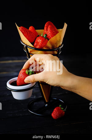 Woman hand holding a strawberry and dipping chocolate. Dessert concept on a fancy support, isolated on the dark background - Stock Photo