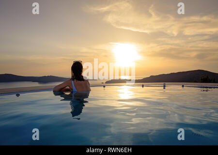 Woman in infinity swimming pool at golden sunset. Girl admiring sunset from the pool. Summer vacation holiday - Stock Photo