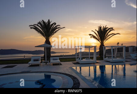 Santorini, Cyclades islands / Greece - 16 May 2018: swimming pools in a luxury resort at golden sunset in Oia - Stock Photo