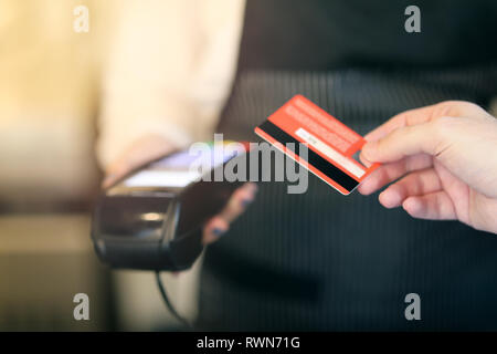 Cropped shot of an unrecognizable man paying for his purchase by contactless card. Soft focus on card - Stock Photo