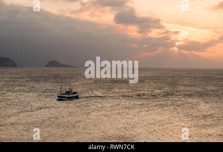 Fishing boat entering during sunset, to the port of Aviles, Asturias, Spain - Stock Photo