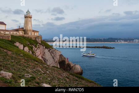 Fishing boat entering during sunset,sailing in front of the lighthouse of Saint Juan, to the port of Aviles, Asturias, Spain - Stock Photo