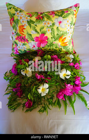 Arrangement of fresh tropical flowers placed on a bed in a luxury hotel in Bora Bora, French Polynesia - Stock Photo