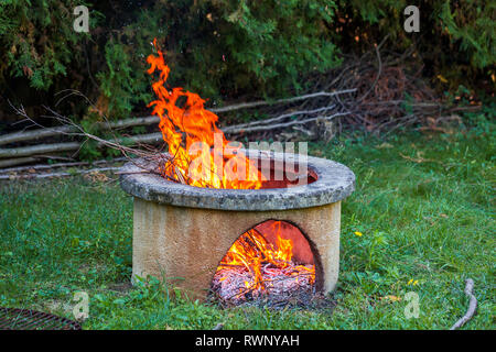 Dry branches burn in isolated campfire pit in the garden. High bright flames flickering on open garden fire pit. - Stock Photo