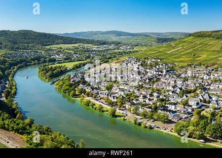 View of riverside village with bend in the river and steep vineyard slopes in the background and blue sky; Bernkastel, Germany