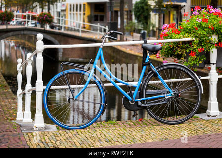 Bike along white metal railing on stone bridge with colourful flowers in box and canal in the background below; Delft, South Holland, Netherlands - Stock Photo
