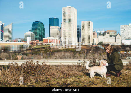 Woman walking her dog with a city skyline in the background; Edmonton, Alberta, Canada - Stock Photo
