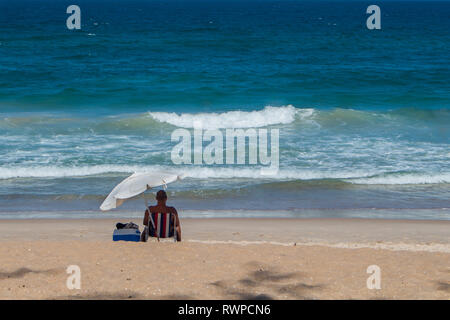 Enjoying the day on the beach under a parasol in a hot day in Floripa. - Stock Photo