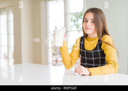 Beautiful young girl driking a glass of fresh milk with a confident expression on smart face thinking serious - Stock Photo
