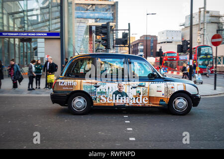 Side view of  Sign written advertising on a Black English Taxi cab in Oxford Street, London - Stock Photo