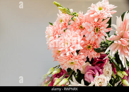 Very beautiful tender blossoming bouquet of fresh hydrangea, eustoma, roses, eucalyptus flowers in pastel pink and cream colours on the grey wall - Stock Photo