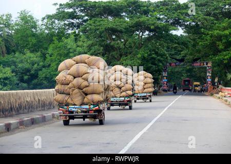 Sacks of onion loaded on the locally assembled tricycle called Nachimon on the Faridpur-Gopalganj highway. Faridpur, Bangladesh. - Stock Photo