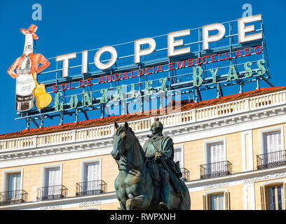 The landmark Tio Pepe sign above Puerta del Sol Square with the statue of Carlos III Charles III of Spain in Madrid - Stock Photo