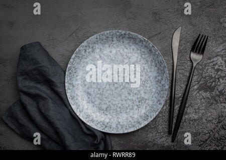 Stylish table setting with black cutlery. Empty plate, table textile and black cutlery on black concrete background. Top view. Restaurant, menu, cafe  - Stock Photo