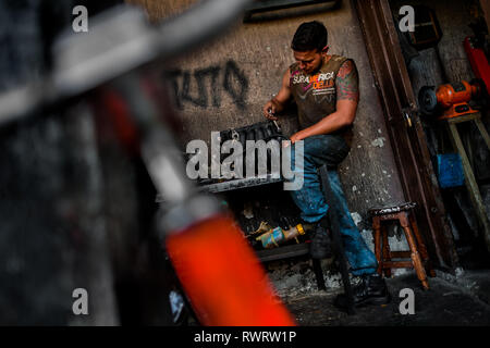 A Colombian car mechanic works on an engine in a car repair shop in Barrio Triste, Medellín, Colombia. - Stock Photo