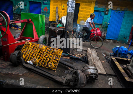 A Colombian car mechanic rides a bicycle through Barrio Triste, a car mechanics neighborhood in Medellín, Colombia. - Stock Photo
