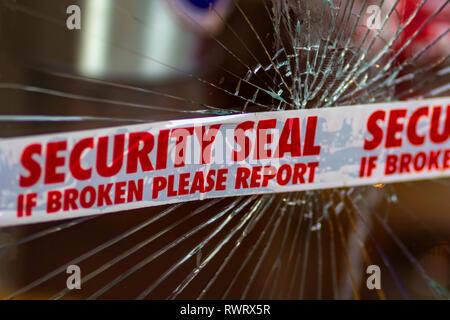 Police Security Seal tape across broken glass window - Stock Photo