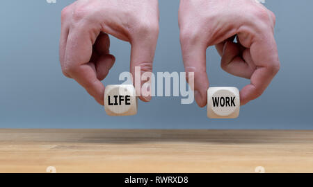 Symbol for finding the right balance between work and life. Two Hands hold two dice with the words 'life' and 'work'. - Stock Photo