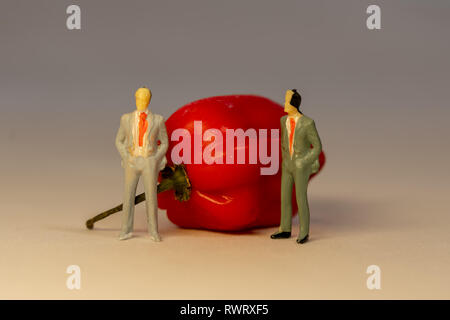 Two miniature business men in suit standing in front of the red hot Habanero pepper. Business conflict concept - Stock Photo