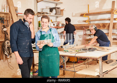 Young craftsman using tablet computer online in joinery workshop - Stock Photo