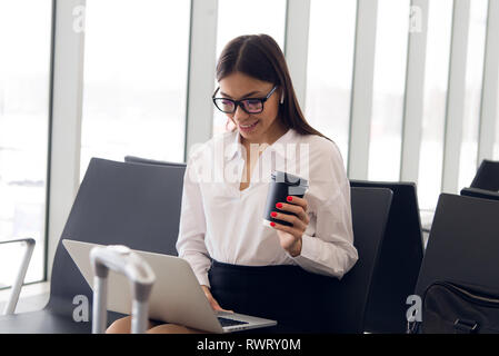 Breaktime business. Beautiful business woman working on laptop while waiting for her flight in an airport. - Stock Photo