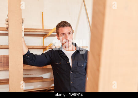 Young man as a joiner or carpenter works in the carpentry workshop - Stock Photo