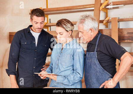 Schreiner team with trainee planning with tablet computer in the joinery - Stock Photo