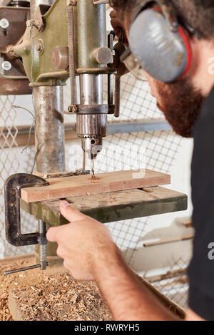 Joiner or carpenter is drilling a hole in a wood board with a power drill - Stock Photo