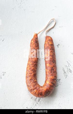 Spanish chorizo sausage on the white background - Stock Photo