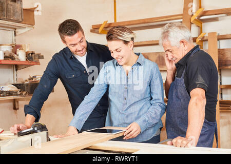 Craftsman team and wife as apprentice using tablet computer in joinery workshop - Stock Photo