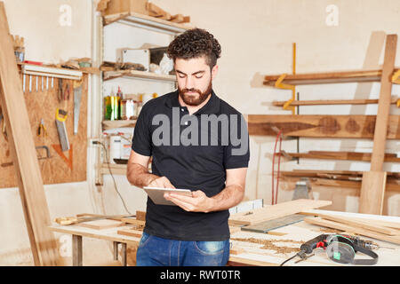 Young craftsman in the workshop with the tablet computer writes an email - Stock Photo