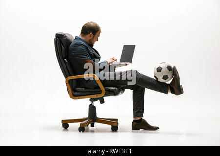 Businessman with football ball in office. Soccer freestyle. Concept of balance and agility in business. Manager perfoming tricks sitting on chair and working on laptop isolated on white studio background. - Stock Photo