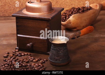 Old wooden scoop with coffee beans, coffee grinder and Turkish coffee in Cezve on dark stone table. - Stock Photo