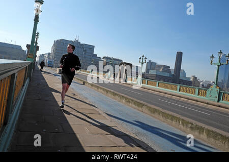 Man in lycra running across Southwark Bridge with a view of the Tate Modern building on a sunny winter day in City of London England UK  KATHY DEWITT - Stock Photo