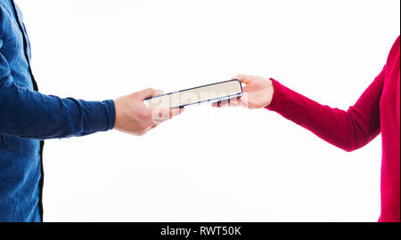 Close up portrait of man and women students exchanging books isolated on white. Literature sharing between people. Give to read to a friend as present - Stock Photo