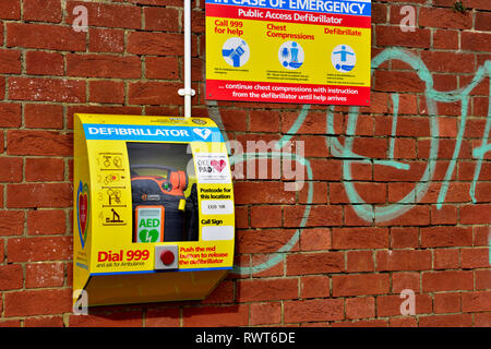 Public defibrillator emergency life saving equipment mounted on outside wall, Okehampton, Devon, England - Stock Photo