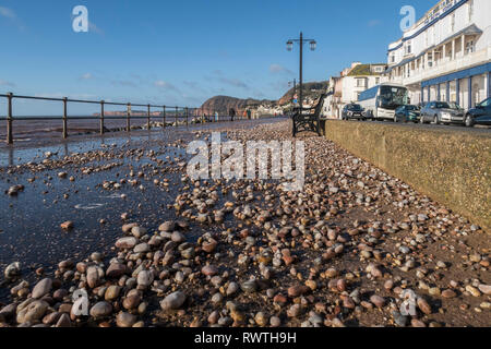 Pebble and shale from the beach thrown onto the seafront Esplanade at Sidmouth by a storm. - Stock Photo